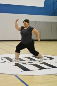 A woman doing Exercises in the clubfit sport fields over the clubfit logo