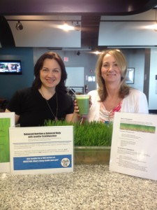 Two woman drinking a green juice.