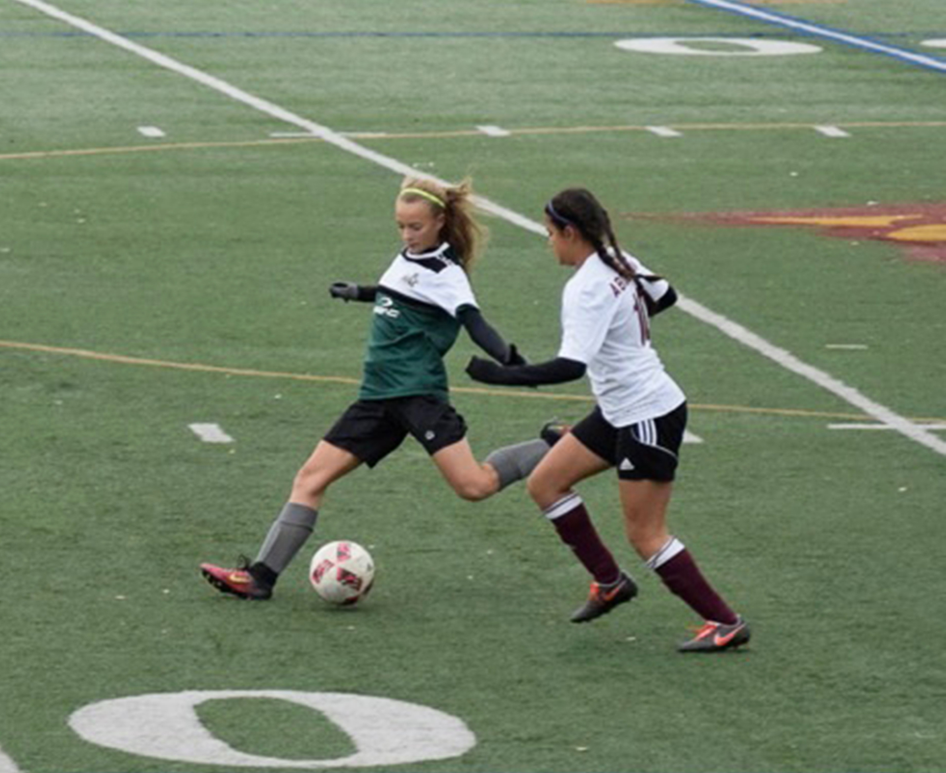 Two girls playing soccer one of them is Chayce Buono