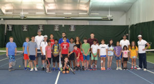 Club Fit Junior Tennis Campers posing with Pros Michael and Brandin in front of the Club's Tennis Champ banners.