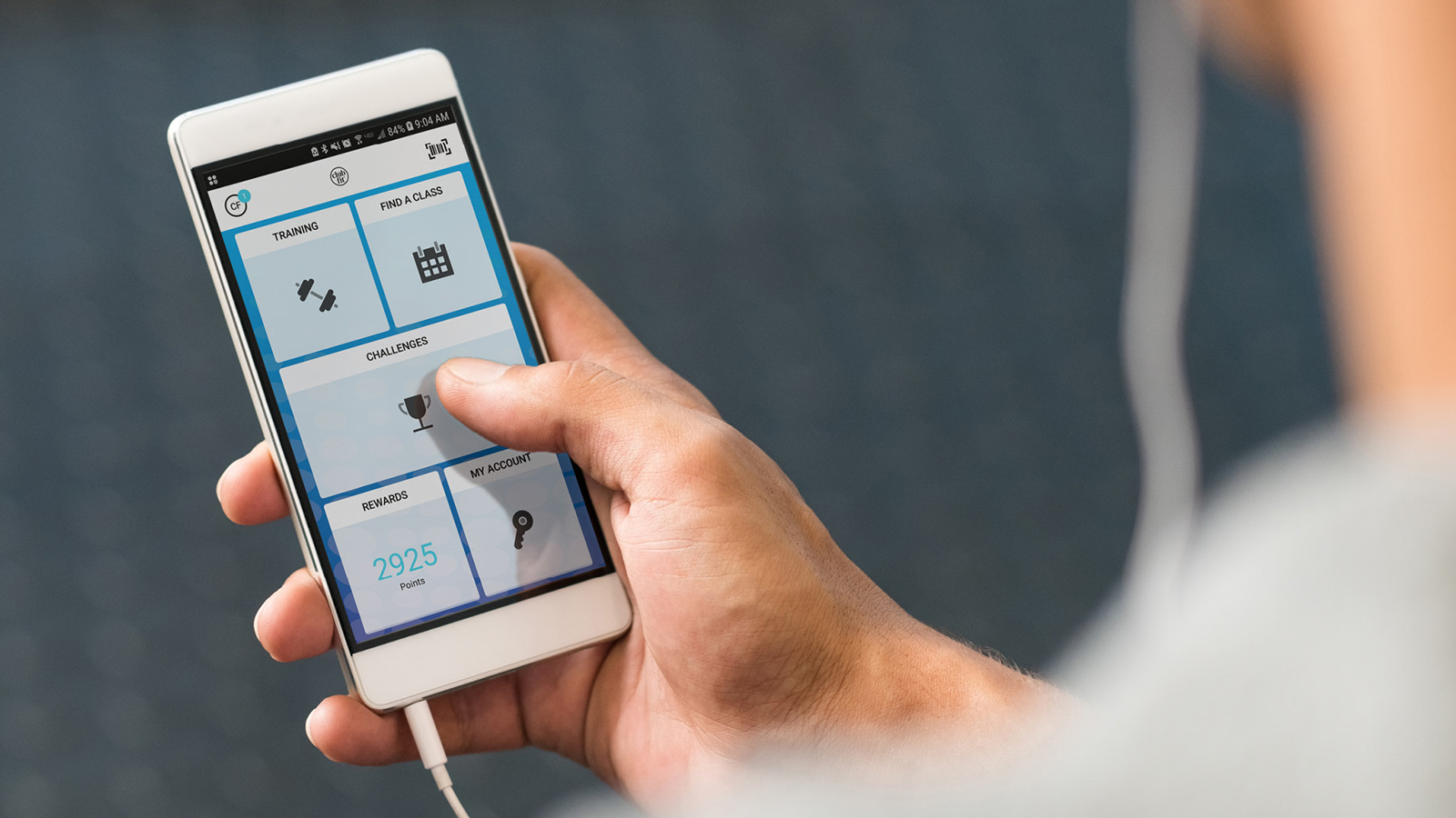 Man in gym using Club Fit app on handheld device